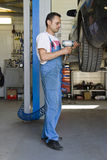 Car mechanic. Mechanic with an impact wrench pneumatic tool working in the garage stock photography