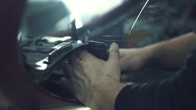 Car mechanic installs protective mesh stock video footage