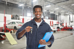 Car mechanic with key. Royalty Free Stock Image