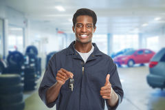 Car mechanic with key. Car mechanic giving auto keys over garage background stock photos