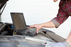 Car mechanic with laptop Royalty Free Stock Image