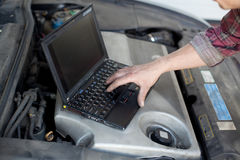 Car mechanic with laptop. Auto mechanic with laptop checking enine royalty free stock images