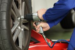 Car mechanic loosen wheel nuts in a workshop. Close up of a car mechanic hands loosen wheel nuts with a pneumatic gun in a mechanical workshop Royalty Free Stock Photography
