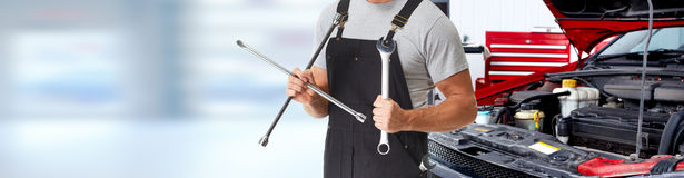 Car mechanic. Car mechanic with lug wrench in auto repair service garage stock image