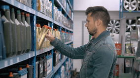 Car mechanic man choose modern car battery for truck at repair service station supermarket. A lot of goods. Car mechanic man choose motor oil stock footage