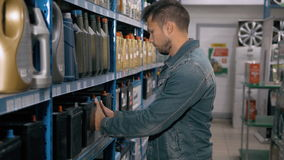 Car mechanic man choose modern car battery for truck at repair service station supermarket. A lot of goods. Car mechanic man choose motor oil stock video footage