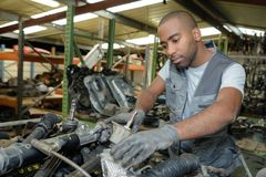 Car mechanic man at garage fixing engine. Car mechanic man at the garage fixing the engine Stock Photos