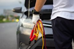 Car mechanic man holding battery jumper cables to charge a dead stock image