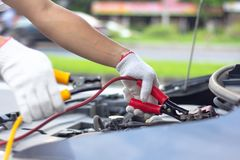 Car mechanic man using battery jumper cables to charge a dead ba royalty free stock photos