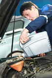 Car mechanic pouring oil into motor engine Royalty Free Stock Image