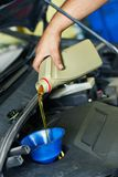 Car mechanic pouring oil into motor engine Stock Photos