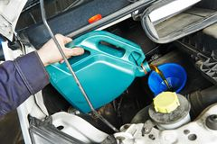 Car mechanic pouring oil into motor engine Royalty Free Stock Photography