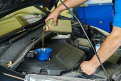 Car mechanic pouring oil into motor engine Stock Image