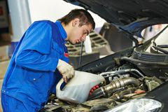 Car mechanic pouring oil into motor engine Royalty Free Stock Photos