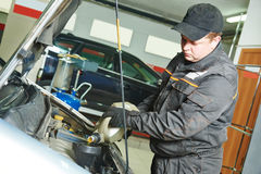 Car mechanic pouring oil into motor engine Royalty Free Stock Images