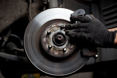 Car mechanic repair brake pads. Closeup of car mechanic repairing brake pads Stock Image