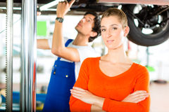 Car Mechanic repairing auto of woman customer Stock Photo