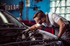 Car mechanic repairing vehicle. Picture of car mechanic repairing broken vehicle Stock Photography