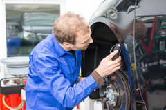 Car mechanic repairs the brakes Stock Photography