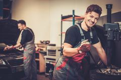 Car mechanic replace tire on wheel in auto repair service. Stock Photos