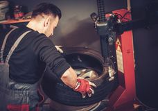 Car mechanic replace tire on wheel in auto repair service. Royalty Free Stock Photo
