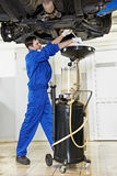 Car mechanic replacing oil from motor engine Royalty Free Stock Photos