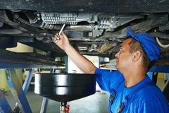 Car mechanic replacing oil from motor engine Royalty Free Stock Image