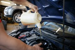 Car mechanic replacing and pouring fresh oil into engine at maintenance repair service station royalty free stock photos