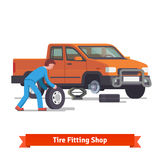 Car mechanic rolling tire to change it Royalty Free Stock Photos