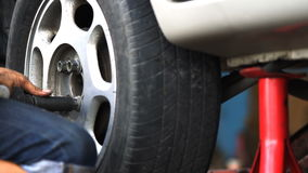 Car mechanic screwing car wheel. By pneumatic wrench stock footage