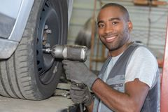 Car mechanic screwing or unscrewing car wheel. Man royalty free stock photos