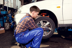 Car mechanic screwing or unscrewing car wheel of lifted automobile by pneumatic wrench. At repair service station stock image