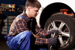 Car mechanic screwing or unscrewing car wheel of lifted automobi Royalty Free Stock Photography