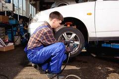 Car mechanic screwing or unscrewing car wheel of lifted automobi Stock Photos