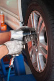 Car mechanic screwing or unscrewing car wheel of lifted automobi Stock Photo