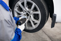 Car mechanic screwing or unscrewing  wheel of lifted automobile by pneumatic wrench at repair service station Stock Photos