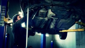 Car mechanic with spanner tighten car suspension detail of lifted automobile. At service repair garage stock video footage