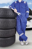 Car mechanic standing with pile of tires. Image of car mechanic wearing blue uniform and standing with a pile of tires, shot outdoors Royalty Free Stock Photography