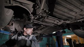 Car mechanic standing under car. In workshop and checking it stock video footage