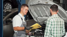 Car mechanic talking to the client at automotive service center. Professional auto mechanic holding clipboard with documents, talking to the client after stock video