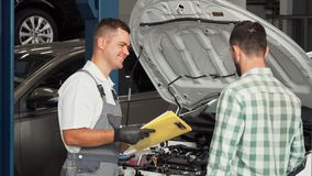 Car mechanic talking to the client at automotive service center. Professional auto mechanic holding clipboard with documents, talking to the client after stock image