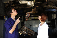 Car mechanic talking to costumer. At the car repair shop stock photos