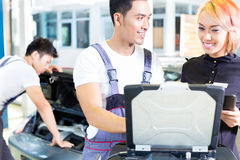 Car mechanic team with diagnosis tool in workshop. Asian Chinese car mechanic team checking auto engine with diagnostics tool in his workshop royalty free stock photo
