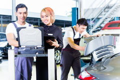 Car mechanic team with diagnosis tool in workshop. Asian Chinese car mechanic team checking auto engine with diagnostics tool in his workshop royalty free stock photography