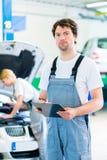 Car Mechanic team working in auto workshop Stock Photo