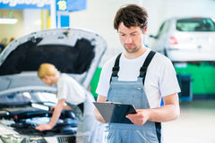Car Mechanic team working in auto workshop Royalty Free Stock Image
