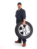 Car mechanic with a tire. Royalty Free Stock Photos