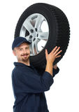 Car mechanic with a tire. Royalty Free Stock Photography