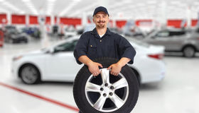 Car mechanic with a tire. Stock Photography