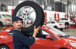 Car mechanic with a tire. Royalty Free Stock Image